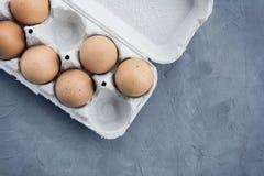 Uova in un vassoio ed in un fondo di legno, vista superiore Immagine Stock Libera da Diritti