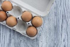Uova in un vassoio ed in un fondo di legno, vista superiore Fotografia Stock Libera da Diritti