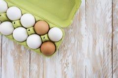 Uova in un vassoio ed in un fondo di legno, vista superiore Immagine Stock