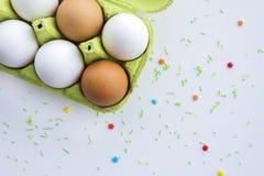 Uova in un vassoio ed in un fondo di legno, vista superiore Fotografie Stock