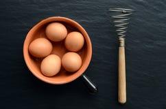 Uova in una ciotola con il frullino per le uova Immagini Stock