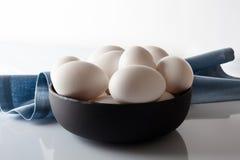 Uova in una ciotola con il tovagliolo blu su bianco Immagine Stock