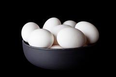 Uova in una ciotola sul nero dal lato Immagine Stock