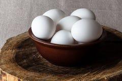 Uova in una ciotola sul tagliere dal lato Fotografie Stock Libere da Diritti