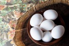 Uova in una ciotola sul tagliere rurale da sopra Fotografia Stock