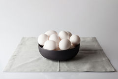 Uova in una ciotola sul tovagliolo beige dal lato Fotografia Stock