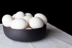 Uova in una ciotola sul tovagliolo bianco da parte Immagine Stock Libera da Diritti