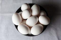 Uova in una ciotola sul tovagliolo bianco da sopra Immagine Stock