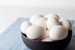 Uova in una ciotola sul tovagliolo blu da parte Fotografia Stock