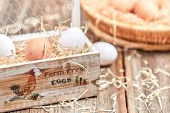 Uova in una scatola delle uova di legno sulla tavola Fotografie Stock