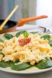 Uova, valerianella e formaggio rimescolati sul piatto Fotografia Stock