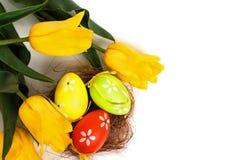 Uova variopinte di Pasqua con i tulipani gialli Immagine Stock