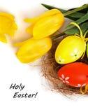 Uova variopinte di Pasqua con i tulipani gialli Immagine Stock Libera da Diritti