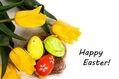 Uova variopinte di Pasqua con i tulipani gialli Fotografie Stock