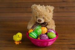Uova variopinte di Pasqua, orsacchiotto e pollo del giocattolo Immagine Stock