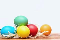 Uova variopinte dipinte di pasqua con il nido della paglia isolato su bianco Immagine Stock Libera da Diritti