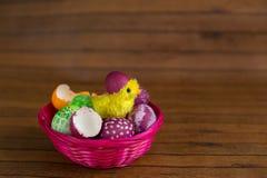 Uova variopinte e pulcino di Pasqua che covano dalle coperture Fotografia Stock