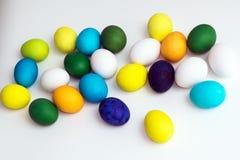 Uova variopinte festive di Pasqua su un fondo bianco le uova ingialliscono, blu, verde e blu, arancio Immagine Stock