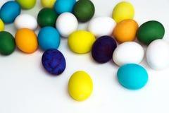 Uova variopinte festive di Pasqua su un fondo bianco le uova ingialliscono, blu, verde e blu, arancio Fotografia Stock Libera da Diritti