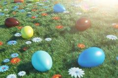 Uova variopinte in un prato un giorno soleggiato, con i bei fiori Uova di Pasqua dipinte multicolori su erba, prato inglese fotografia stock libera da diritti