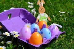 Uova variopinte in una scatola ed in un coniglio Fotografie Stock