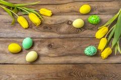 Uova verdi gialle di Pasqua e tulipani, spazio della copia immagini stock