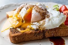 Uovo affogato sul pane del pane tostato con cheddar, aceto balsamico, insalata e sesamo o semi di cumino neri immagini stock libere da diritti
