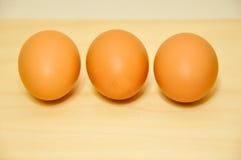 Uovo crudo tre in una fila Fotografia Stock