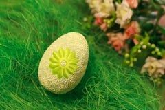Uovo decorativo su erba verde Concetti Pasqua, uova, fiori fatti a mano Immagini Stock Libere da Diritti