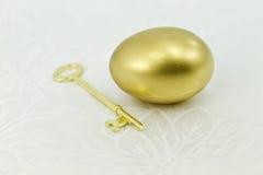 Uovo dell'oro con il tasto su damasco bianco Fotografie Stock Libere da Diritti