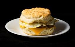 Uovo della salsiccia della prima colazione e biscotto del formaggio su un fondo nero Fotografia Stock