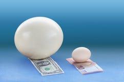 Uovo dello struzzo su un uovo di gallina e di provenienza dalla zona del dollaro sulla banconota dell'euro 10 Fotografie Stock Libere da Diritti