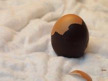 Uovo di cioccolato, coperture parziali dell'uovo, panno bianco Fotografia Stock
