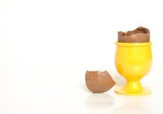 Uovo di cioccolato rotto in tazza Fotografia Stock