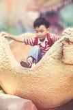 Uovo di dinosauro rampicante di simulazione del ragazzo asiatico Concetto della p all'aperto Fotografia Stock Libera da Diritti