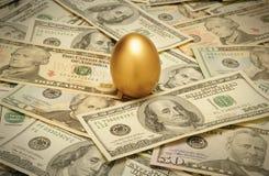 Uovo di nido dell'oro su uno strato di contanti Fotografie Stock