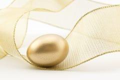 Uovo di nido dorato nel turbinio del nastro dell'oro Fotografia Stock