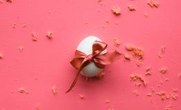Uovo di Pasqua con l'arco festivo su fondo rosa immagini stock libere da diritti