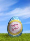 Uovo di Pasqua decorato nell'erba sotto un cielo blu Immagini Stock Libere da Diritti