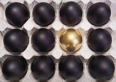 Uovo di Pasqua dell'oro fra molte uova nere Immagini Stock Libere da Diritti