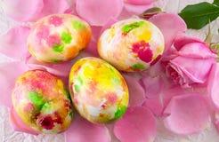 Uovo di Pasqua dipinto sui petali rosa rosa Fotografie Stock