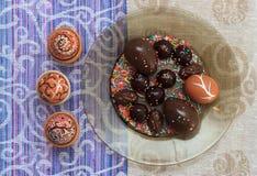 Uovo di Pasqua dipinto variopinto fatto a mano con le caramelle e le uova di cioccolato contro la tovaglia di corrispondenza Immagini Stock Libere da Diritti