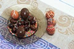 Uovo di Pasqua dipinto variopinto fatto a mano con le caramelle e le uova di cioccolato contro la tovaglia di corrispondenza Fotografia Stock Libera da Diritti