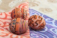 Uovo di Pasqua dipinto variopinto fatto a mano contro la tovaglia di corrispondenza Fotografia Stock