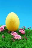Uovo di Pasqua dorato sul prato del fiore & intensamente sul cielo blu piacevole Fotografia Stock
