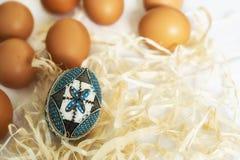 Uovo di Pasqua fatto a mano tradizionale in paglia sul panno bianco Immagine Stock