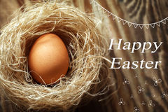 Uovo di Pasqua felice nel nido su fondo di legno Immagini Stock Libere da Diritti