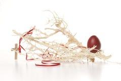 Uovo di Pasqua, filiali e traversa rossi Fotografia Stock