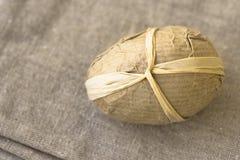 Uovo di Pasqua Handcrafted avvolto in carta marrone del mestiere sul panno di tela, vista superiore Immagine Stock Libera da Diritti