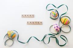Uovo di Pasqua luminoso legato dal nastro verde su fondo bianco Fotografie Stock